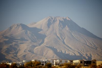 The Hasan Dagi volcano has two peaks towering over the rectangular homes in the valley below. The region around Hasan Dagi, in what is today Turkey, has been inhabited for more than 9,000 years. Photograph by Janet C. Harvey, Public Library of Science