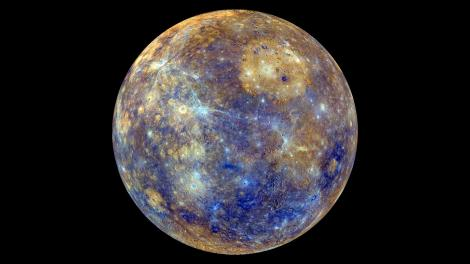 """This breathtaking image of Mercury is not quite what the planet would look like to the human eye. In the image, colors enhance the chemical, mineralogical, and physical differences between the rocks that make up the planet's surface. Young crater rays, extending radially from fresh impact craters, appear light blue or white. Medium- and dark-blue areas are a geologic unit of Mercury's crust known as the """"low-reflectance material"""", thought to be rich in a dark, opaque mineral. Tan areas are plains formed by eruption of highly fluid lavas. The giant Caloris basin is the large circular tan feature located just to the upper right of center of the image. Image by NASA/Johns Hopkins University Applied Physics Laboratory/Carnegie Institution of Washington"""