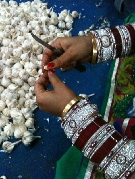 A young bride peels garlic as part of seva. Photograph by Anna Switzer.