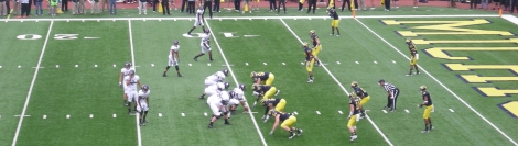 Scholarship players at Northwestern University (in white above, on offense against the University of Michigan in 2012) were recognized as university employees in a National Labor Relations Board (NLRB) decision in February. As employees, they have the right to form or join a labor union. Photograph by Michael Barera, courtesy Wikimedia. This file is licensed under the Creative Commons Attribution-Share Alike 3.0 Unported license.