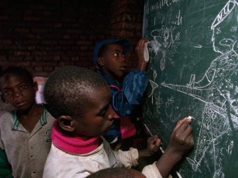 "A Hutu boy, orphaned by the war in Rwanda, draws pictures of Tutsi-led Rwandan Patriotic Front soldiers shooting small stick figures who represent Hutus. Many Rwandan Hutus think their role in the Rwandan civil war is being re-written in an ""official narrative"" school curriculum. Photograph by Michael Nichols, National Geographic"