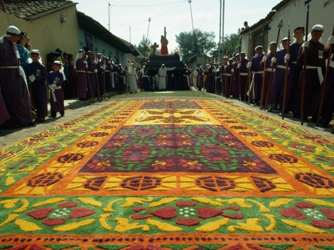 """Sawdust carpets,"" like this one in the historic city of Antigua, line city streets in Guatemala each year during Holy Week, the week that precedes the Christian festival of Easter. Artists use wooden stencils to create the intricate designs. The designs themselves use fine, colored sawdust. Religious processions then pass through the carpeted streets, reducing the work to dusty memories. Photograph by Joe Scherschel, National Geographic"