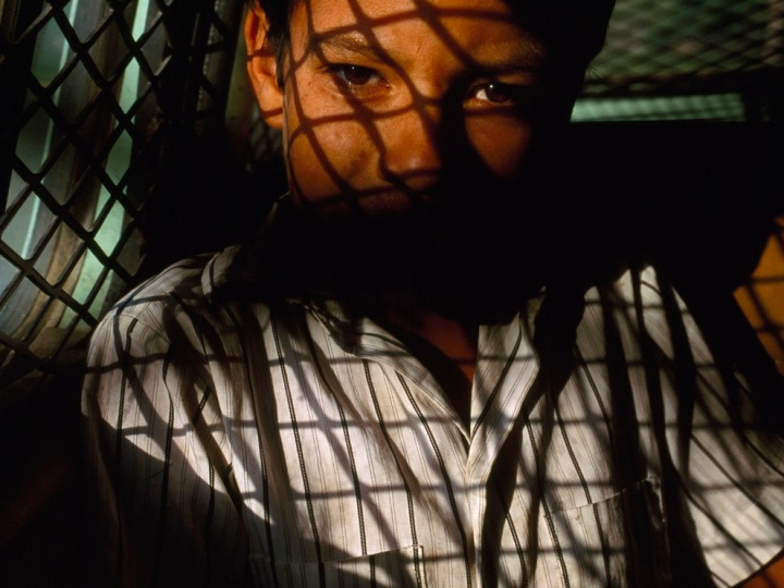 Shadowed by the containment bars of a Border Patrol car, a 10-year-old boy is driven back to his hometown of Matamoros, Tamaulipas, Mexico, after being picked up in Brownsville, Texas. Photograph by Joel Sartore, National Geographic