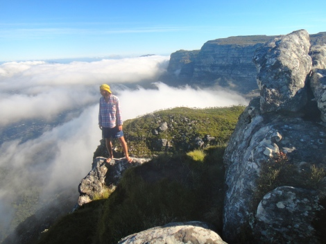 Clouds conceal Cape Town as a student looks out from the summit of Devil's Peak