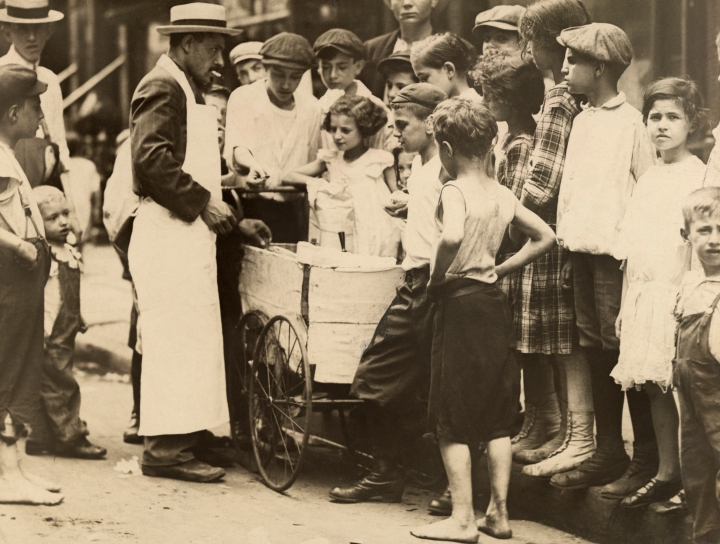 A man sells ice cream to children from a cart during the summer of 1918. Photograph by Paul Thompson, National Geographic.