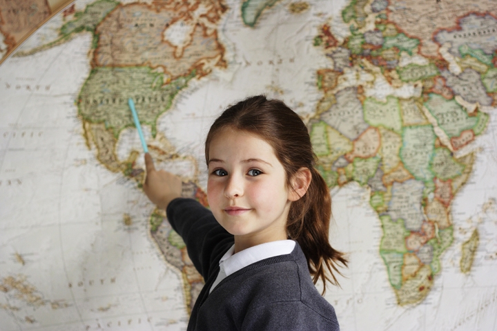 young girl points to United States on map