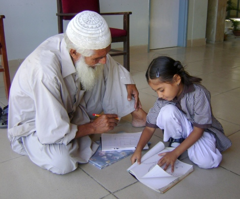 """6 Year Old Teacher, 70 Year Old Student"" - photograph taken at Korangi Academy in Karachi, Pakistan, one of Chris Baer's partner schools. Photograph by Babar Ali"