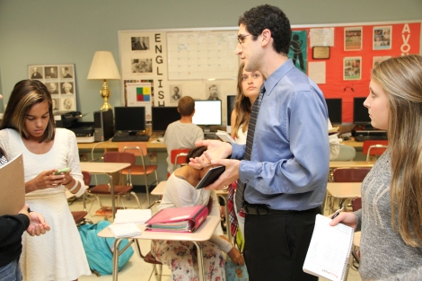 Scott's current Journalism 1 students check online for background information and listen to a final reporting suggestion before leaving to complete interviews, a skill bolstered by global dialogue through PenPal Schools. Photograph by current Journalism 1 student Ethan Woodfill.