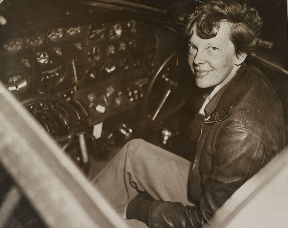 Amelia Earhart smiles at the controls of her modified Lockheed Electra ...