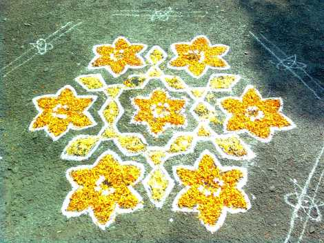 Many artists create rangoli using flower petals. This design was created with chalk and marigold petals. Photograph by Adityamadhav83, courtesy Wikimedia (CC-BY-SA-3.0)