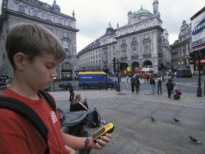 A young American uses a GPS device to navigate the city of London, England. A GPS (global positioning system) unit uses information from United States satellites to provide an accurate location almost anywhere on Earth.