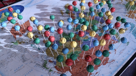 Cake pops represent data points on a National Geographic world map.