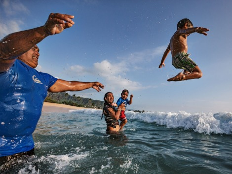 "From cradle . . . On a day off from his job as a beach lifeguard, Mel Pu'u plays with three of his eight kids in the Makaha surf. ""I grew up in the ocean. So did all my children,"" he says. Photograph by Paul Nicklen, National Geographic"