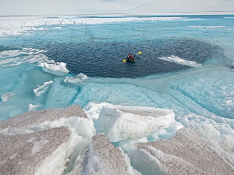 A National Geographic writer crosses a supraglacial lake above a moulin 96 feet deep. Meltwater lakes like this one may become more familiar parts of the Greenlandic landscape. Photograph by James Balog, National Geographic