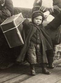 An immigrant boy carries luggage at Ellis Island. Photo by Paul Thompson