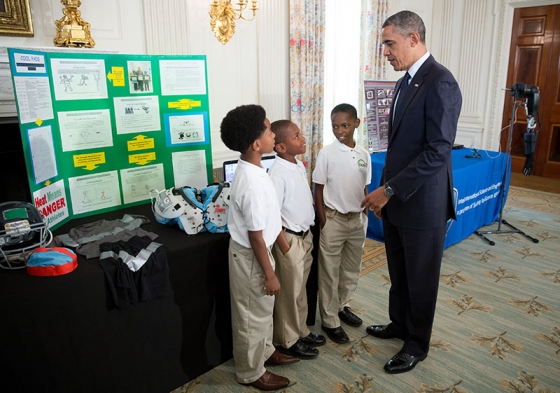 President Barack Obama talks with Evan Jackson, 10, Alec Jackson, 8, and Caleb Robinson, 8, from McDonough, Georgia, while looking at exhibits at the 2013 White House Science Fair. The sports-loving grade-schoolers created a new product concept to keep athletes cool and help players maintain safe body temperatures on the field. Official White House Photo by Chuck Kennedy