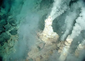 Liquid carbon dioxide bubbles up from fractures adjacent to white-smoker chimneys around NW Eifuku, a submarine volcano. Image courtesy of the NOAA Vents Program