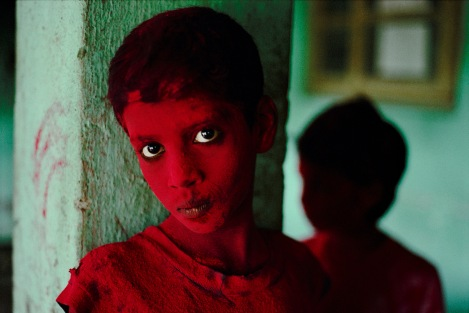 An Indian boy is dusted with red powder during the Hindu festival Ganesh Chaturthi.Photograph by Steve McCurry, National Geographic