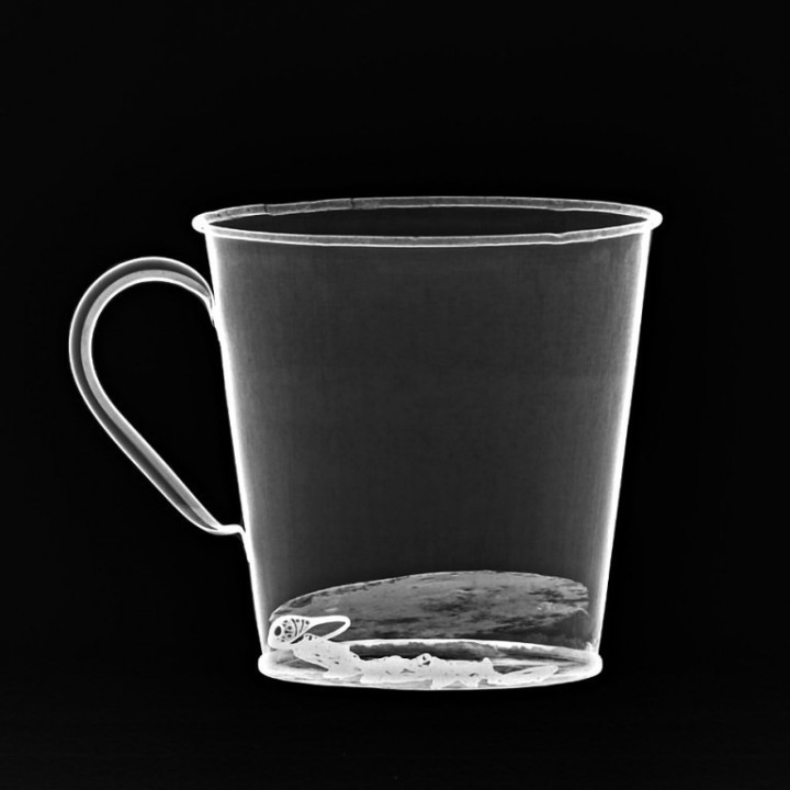 An X-ray reveals jewelry concealed behind the false bottom, which separated from the mug after more than 70 years. Photograph courtesy Auschwitz Museum