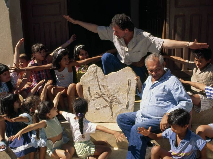 "Dr. Alexander Kellner and local museum founder Placido Cidade Nuvens show the next generation of paleontologists a pterosaur fossil found near their village on the Araripe Plateau in northeastern Brazil. Kellner helps demonstrate how pterosaurs became ""Lords of the Brazilian Sky""—the name of one of his books. Photograph by Jonathan Blair, National Geographic"