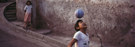 A young girl watches a boy demonstrating his soccer skills.