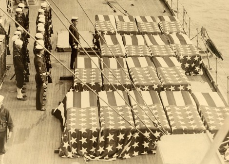 Sailors stand at attention before flag draped coffins during World War I.