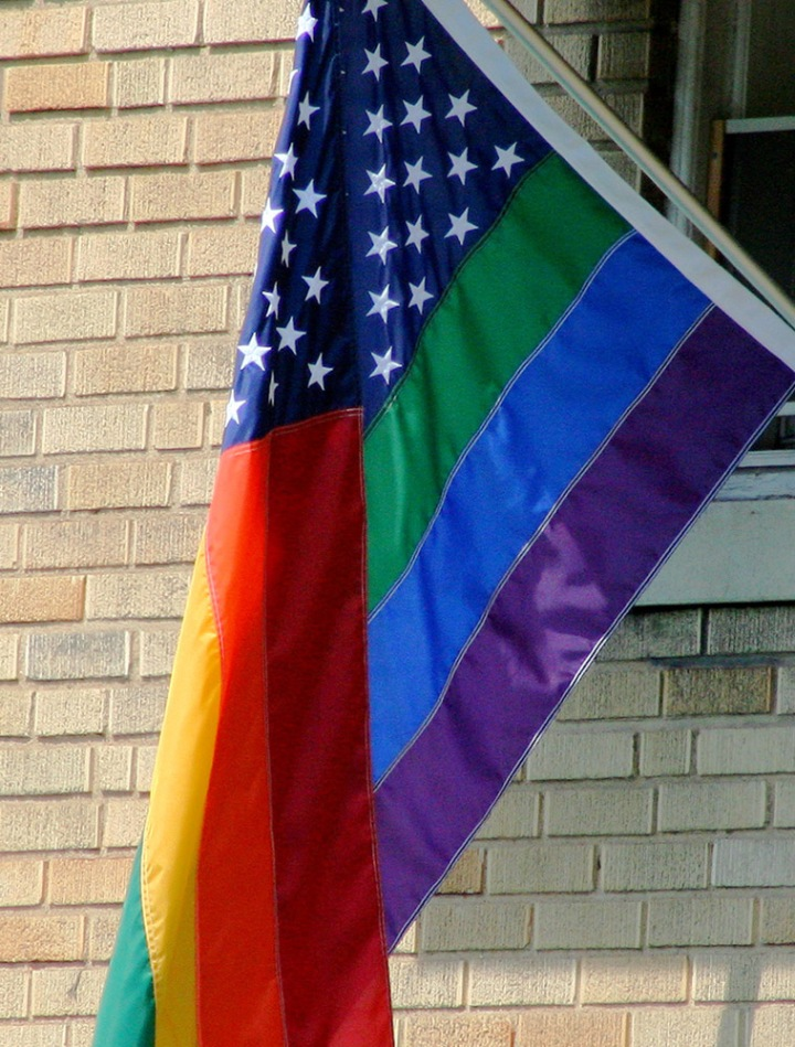 "The six colors of the LGBT rainbow flag symbolize life (red), healing (orange), sunlight (yellow), nature (green), serenity (blue), and spirituality (purple). The white stars on the U.S. flag symbolize the 50 states, and their position on a blue background symbolizes, in the words of Ben Franklin and John Adams, ""a new constellation."" Photograph by dbking, courtesy Wikimedia. CC-BY-2.0"