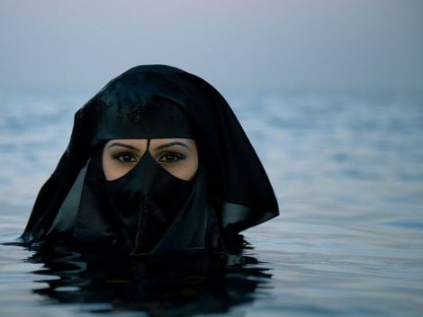 Women who wear hijab coverings often keep them on whenever they are in public—even swimming, as this woman is doing off Saudi Arabia's coast. Like many Saudi women, she is wearing a head scarf called a niqab and an abaya. An abaya covers the entire body except the head, feet, and hands. Photograph by Sebastian Farmborough, My Shot