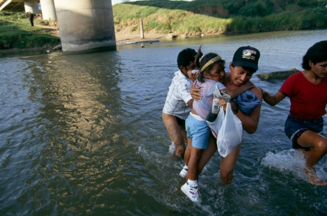 "Coyotes are ""people smugglers"" who help immigrants like these cross the border from Mexico to the United States. (These immigrants are crossing the Rio Grande beneath the International Bridge, leaving Matamoros, Mexico, and entering Brownsville, Texas.) Photograph by Joel Sartore, National Geographic"