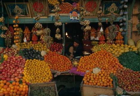 Fruit stand overflows with citrus, pomegranates, eggplants and grapes.