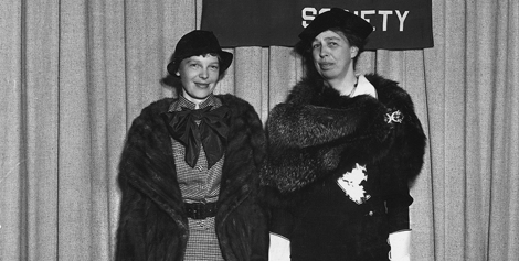 Amelia Earhart and First Lady Eleanor Roosevelt pose by NGS flag at a luncheon in 1935.