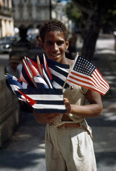 Ten years before the Cuban Revolution in 1959 (count the number of stars on that American flag!), a young man sells flags in Havana. Photograph by Melville B. Grosvenor, National Geographic