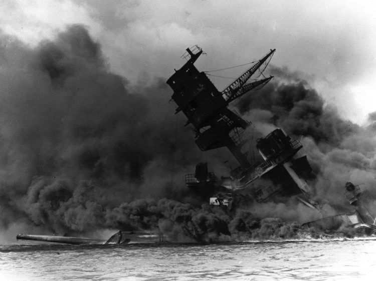 """""""When a bomb blasted the Arizona's forward magazine, the ship disappeared in a thousand-foot mountain of boiling, bluish-purple smoke."""" The ship burned for two days, and 1,177 crew members were killed. It remains the greatest loss of life on any warship in American history. Photograph courtesy the National Park Service, The USS Arizona Memorial Photo Collection"""