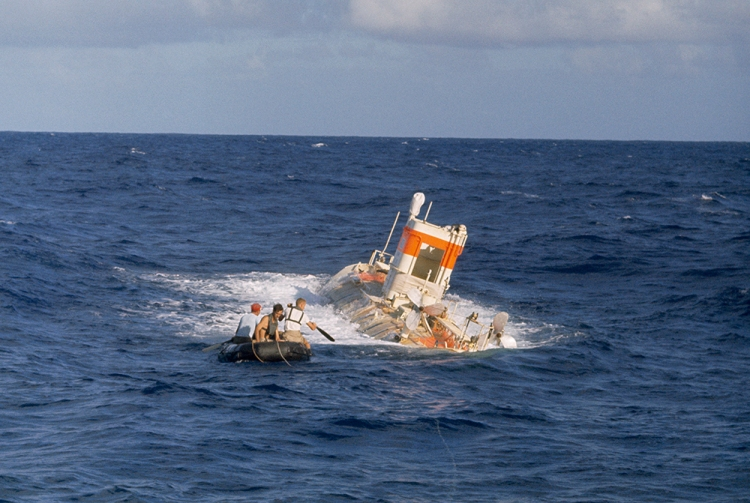 Jacques Piccard and his team paddle toward their bathyscaph submarine in the Mariana Trench, near Guam. Photograph by Thomas J. Abercrombie, National Geographic.
