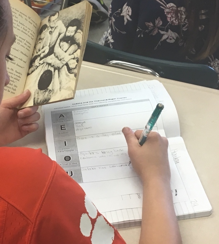 A student refers to a book while writing responses