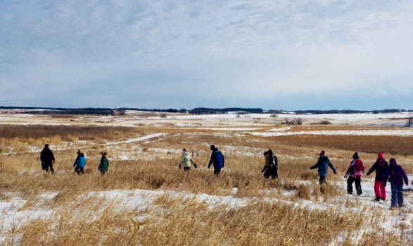 Students walk through the snow-covered prairie