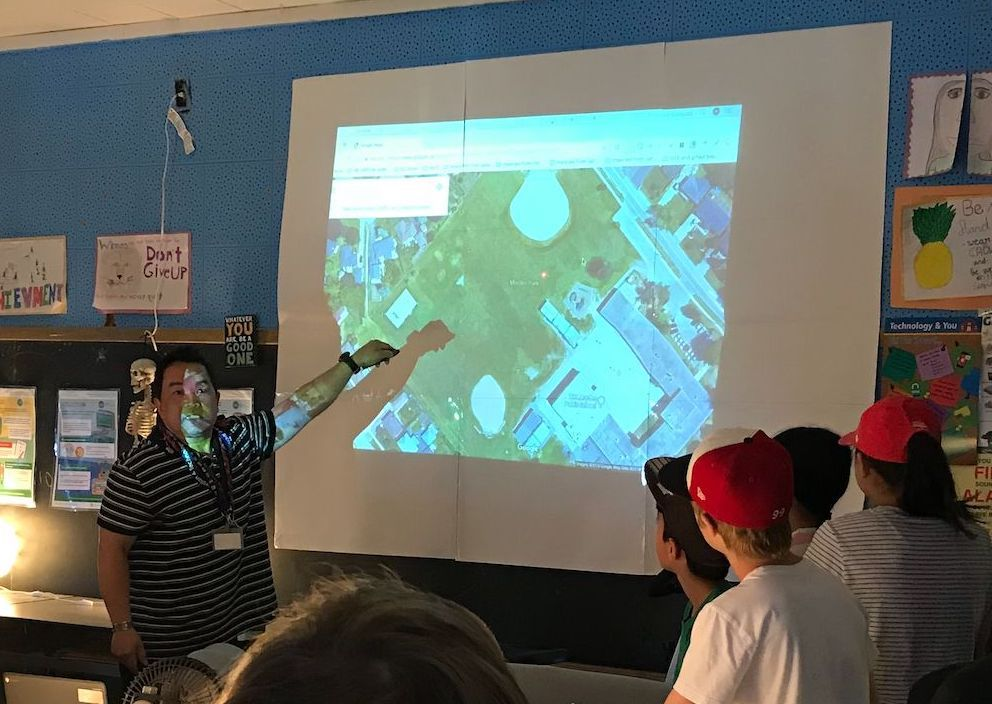 Reggie Vasquez points to a projection of Google Earth as students look on