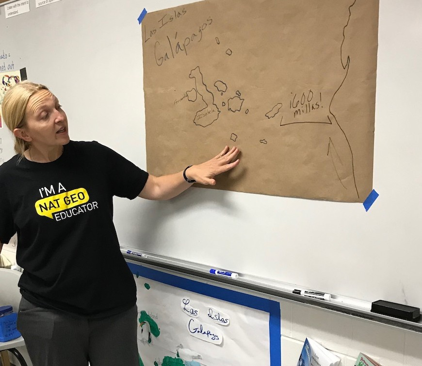 "Abra Koch points to a hand-drawn map titled ""Las Islas Galápagos"" and taped to a whiteboard in a classroom"